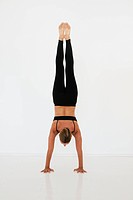 A woman doing a handstand on a white background, tarifa, cadiz, andalusia, spain