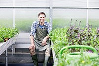 Germany, Bavaria, Munich, Mature man in greenhouse between rocket plant (thumbnail)