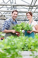 Germany, Bavaria, Munich, Mature man and woman in greenhouse with rocket plant, smiling, portrait