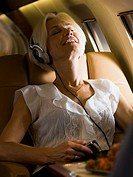 A businesswoman listening to music from an MP3 player in an airplane
