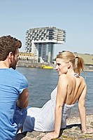 Germany, Cologne, Young couple sitting on riverbank