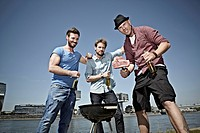 Germany, Cologne, Young men gathered around barbecue and drinking beer