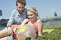 Germany, Cologne, Couple looking at globe, smiling