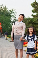 Chinese mother walking with daughter in school uniform