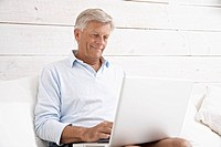 Spain, Senior man checking emails on laptop, smiling