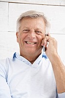 Spain, Senior man talking on mobile, smiling, portrait