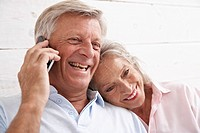 Spain, Senior couple talking on mobile phone, smiling