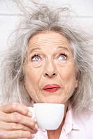 Spain, Senior woman drinking coffee, close up