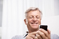 Spain, Senior man checking emails on mobile, smiling