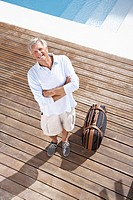 Spain, Senior man standing with suitcase at swimming pool