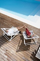 Spain, Senior couple relaxing on deck chair at beach