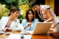 Three women having meeting in restaurant using laptop