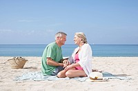 Spain, Senior couple sitting on beach (thumbnail)