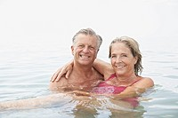 Spain, Senior couple swimming in sea