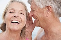 Spain, Senior man whispering into ear of woman, smiling