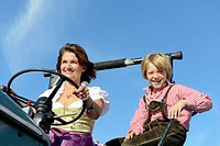 Germany, Bavaria, Mother and son driving tractor