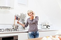Germany, Bavaria, Munich, Woman using mobile in kitchen and preparing food