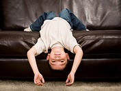 Young boy lying upside down on a leather sofa