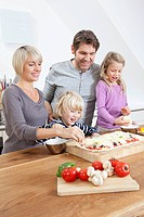 Germany, Bavaria, Munich, Family preparing pizza in kitchen