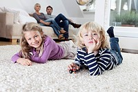 Germany, Bavaria, Munich, Boy and girl lying on floor, parents sitting of couch in background
