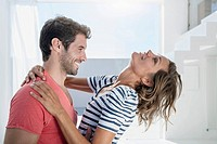 Spain, Mid adult couple embracing each other in modern apartment (thumbnail)