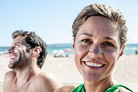 Spain, Mid adult couple sitting at beach, smiling (thumbnail)
