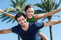 Spain, Mid adult man giving piggy back ride to woman, smiling (thumbnail)