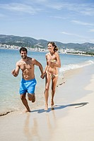 Spain, Mid adult couple running on beach