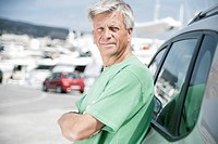 Spain, Senior man leaning on car