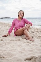 Spain, Senior woman sitting on beach