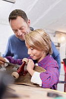 Germany, Leipzig, Father and son repairing skateboard (thumbnail)