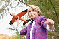 Germany, Leipzig, Boy playing with toy aircraft