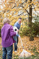 Germany, Leipzig, Boy holding football, father collecting leaves