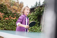 Germany, Leipzig, Boy playing table tennis, smiling