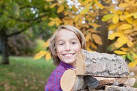 Germany, Leipzig, Boy holding firewood, smiling