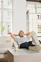 Germany, Berlin, Young man sitting in living room, smiling