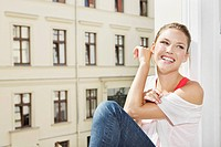 Germany, Berlin, Young woman sitting at open window, smiling