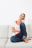 Germany, Berlin, Young woman sitting on couch and using smart phone (thumbnail)