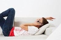 Germany, Berlin, Young woman lying on couch and using smart phone