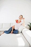 Germany, Berlin, Young woman sitting on couch, smiling