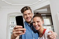 Germany, Berlin, Young man and woman using smart phone, smiling
