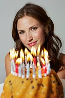 Germany, Berlin, Young woman showing birthday cake, smiling, portrait