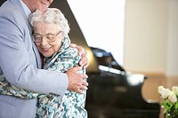 Senior couple embracing in front of piano