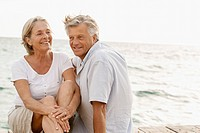 Spain, Senior couple sitting at the sea, smiling