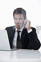Spain, Businessman talking on mobile phone, smiling