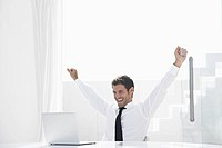Spain, Businessman excited while looking laptop, smiling