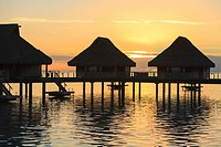 Silhouette of huts over the water at sunset at the bora bora nui resort & spa, bora bora island society islands french polynesia south pacific