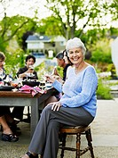 Mature woman with family at outdoor dining table