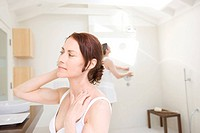 Woman looking at herself in bathroom mirror.