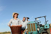 Germany, Bavaria, Farmer couple with tractor and basket of apples